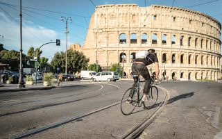 a man cycles in front of the colosseum in rome italy