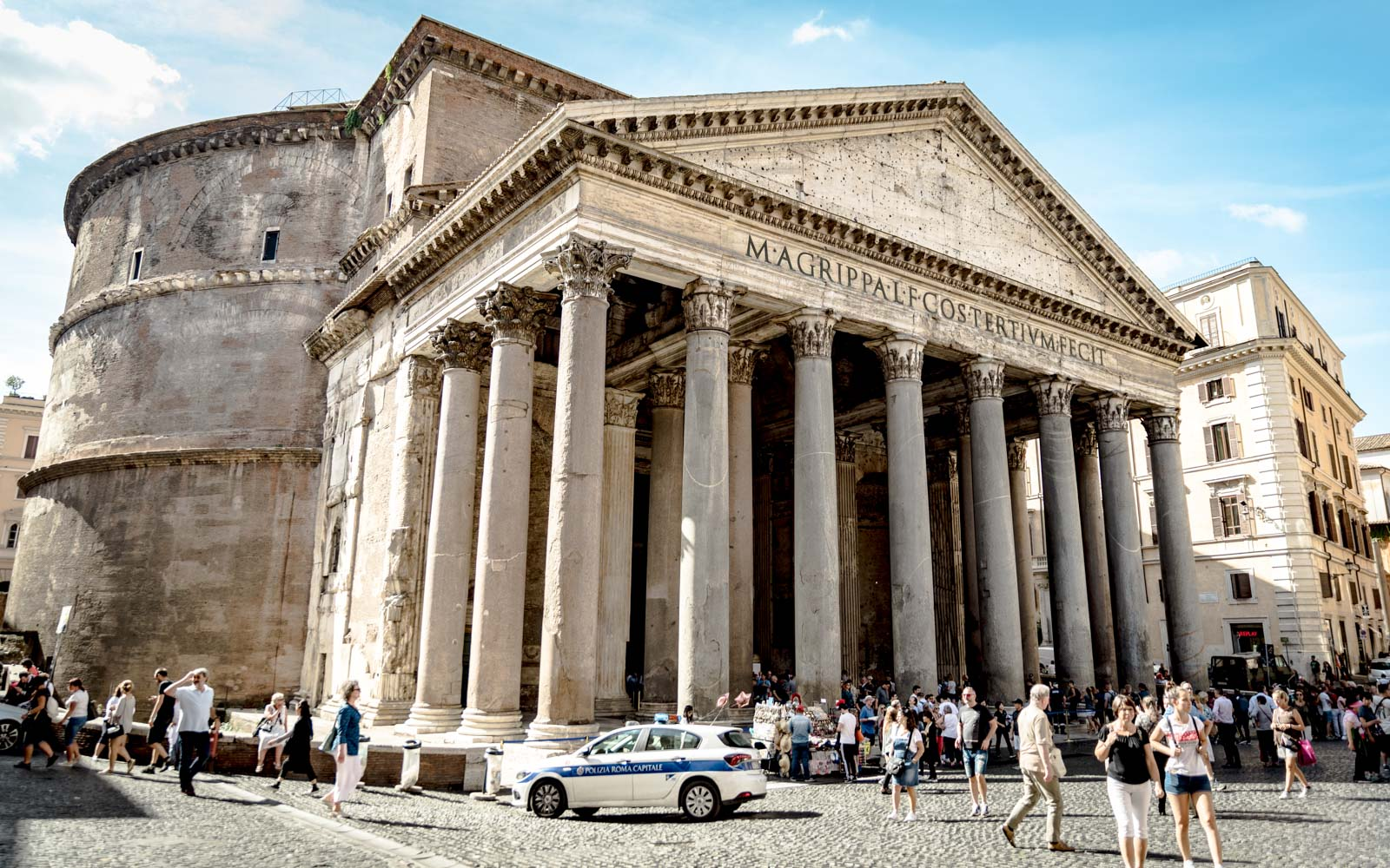 tourists congregate outside the pantheon on a sunny day in rome italy