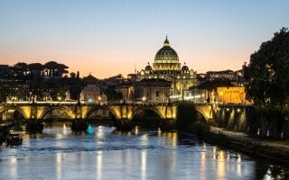 a sunset view of the tiber river with church dome in background in rome italy
