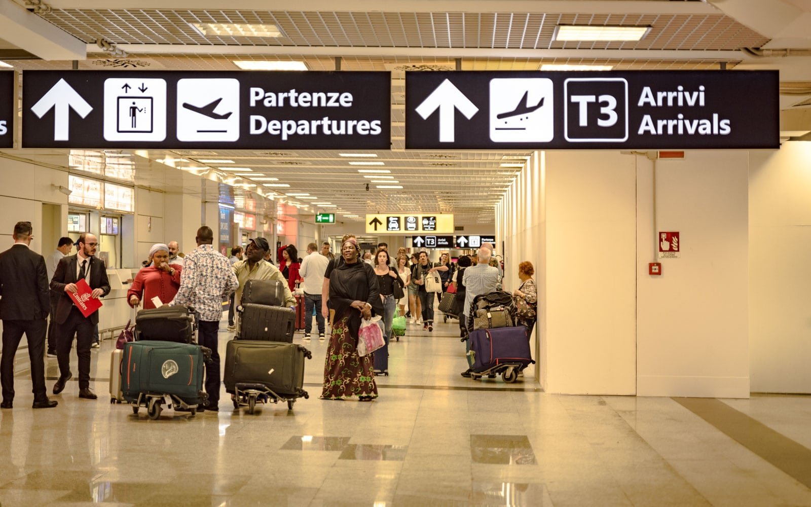 travellers walking with suitcases at fiumicino airport in rome italy
